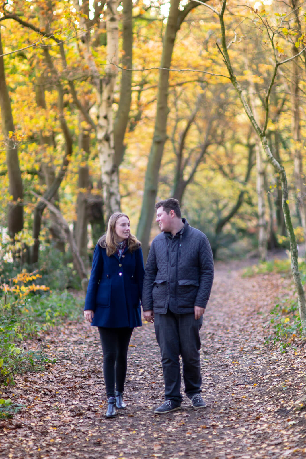 Young engaged couple walking on a woodland path and talking