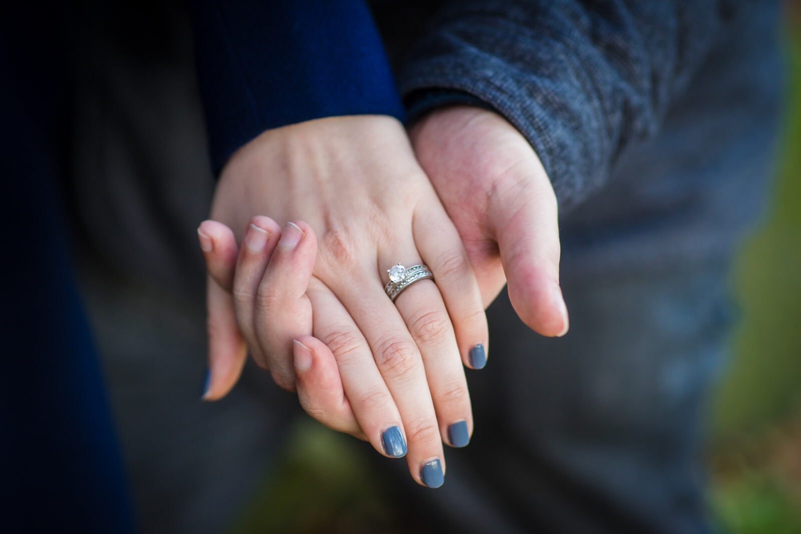engaged couples hands showing her solitaire engagement ring and blue nails