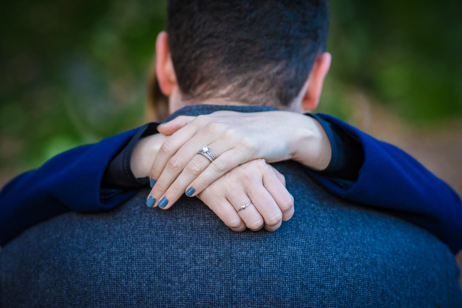 Lady's hands around her fiance's neck with enggagement ring and blue nails