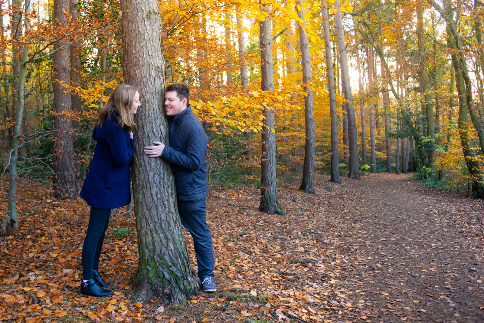Young couple peeking around a tree trunk at each other