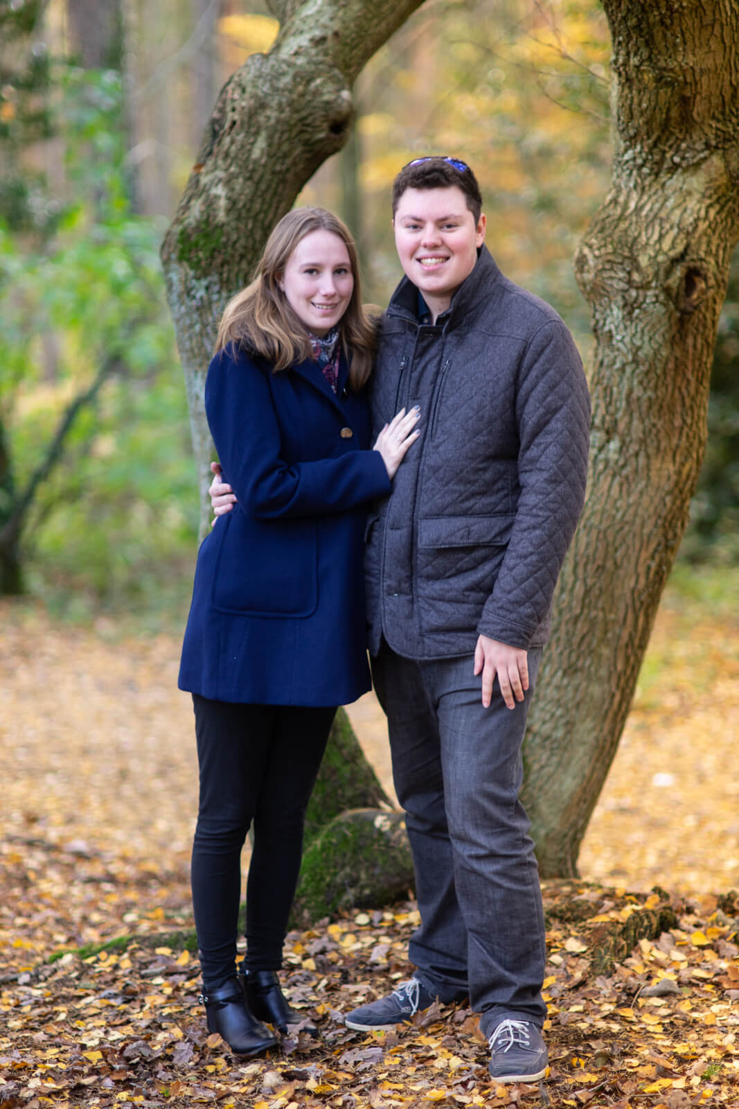 Young engaged couple standing in front of a tree in a wood