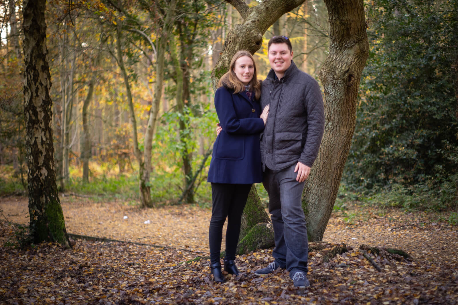 Young engaged couple standing in a wood in the autumn
