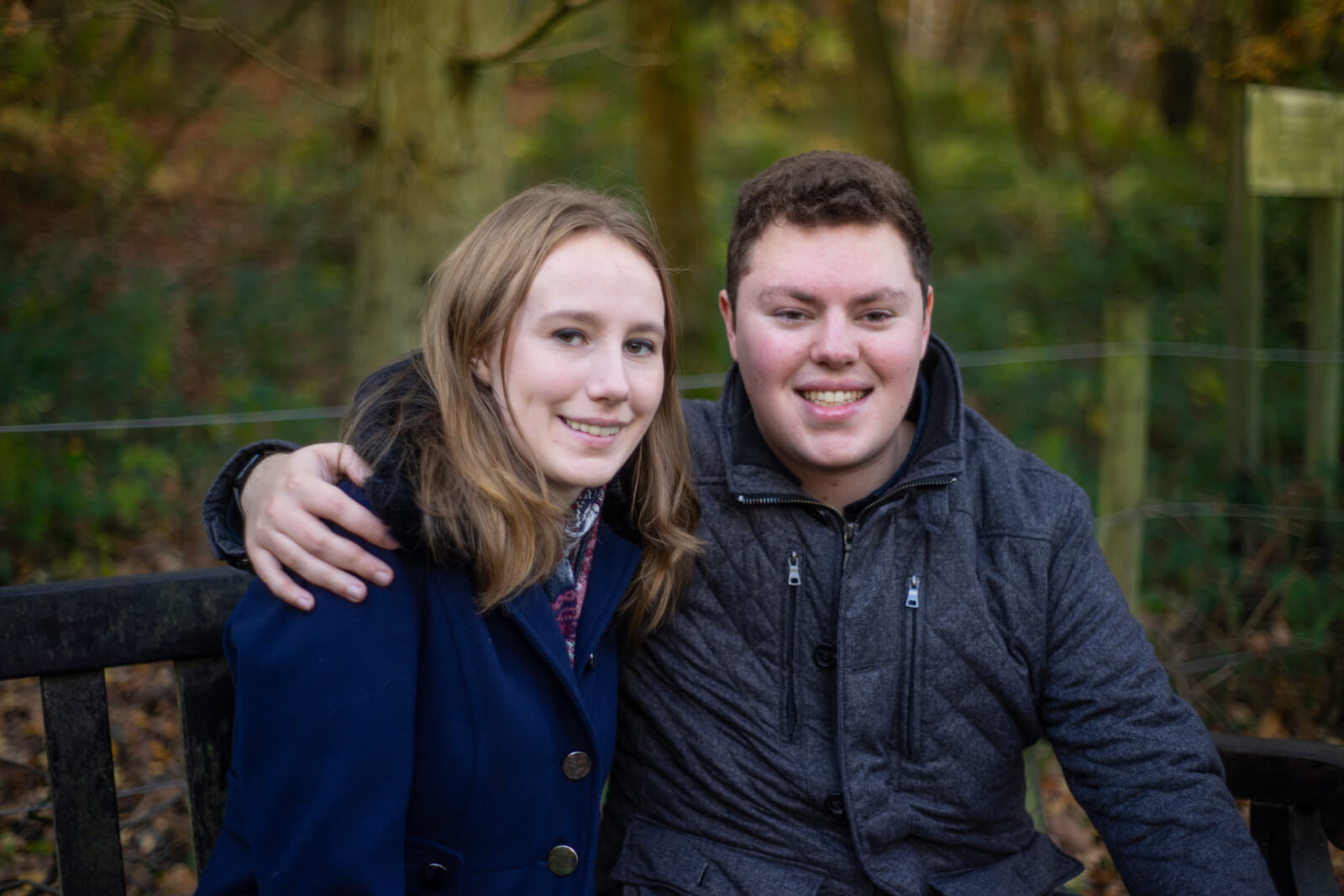 Young man with his arm around his fiance sitting on a bench in woodland