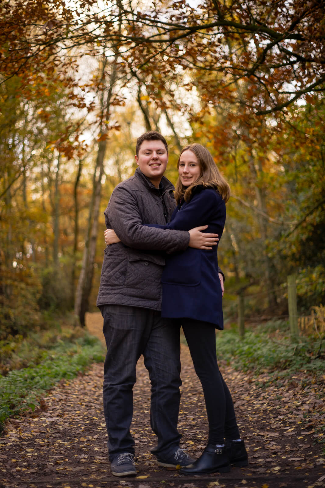 Young couple hugging surrounded by autumnal trees