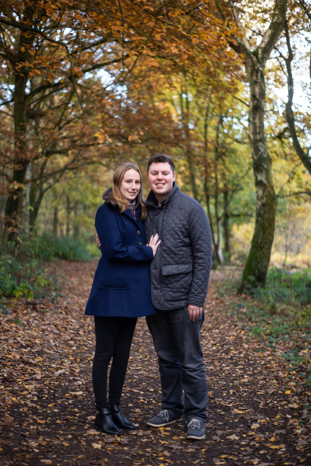Engagement photo of a young couple on a woodland path