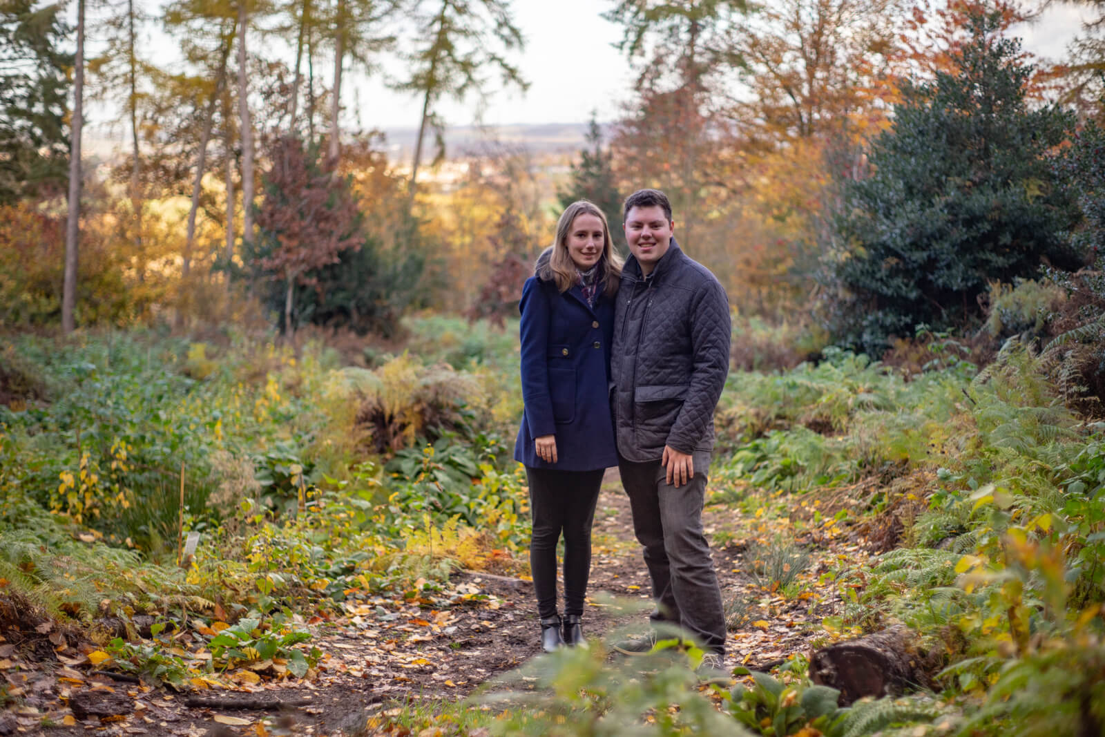 Engagement photo of a couple in a woodland clearing with a view of the hills behind
