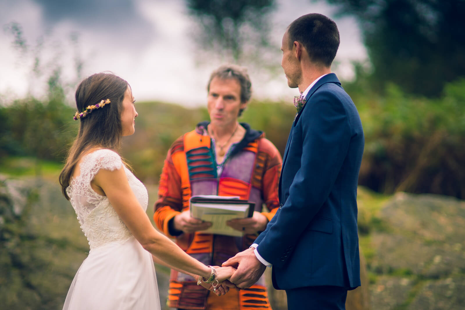 Bride and groom hold hands in front of a colouful celebrant