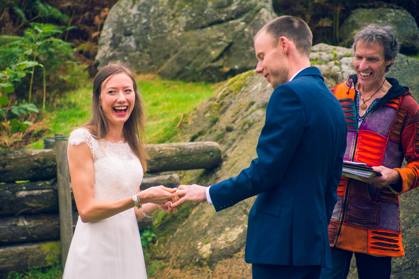 Bride laughs trying to fit the wedding ring onto the groom's finger