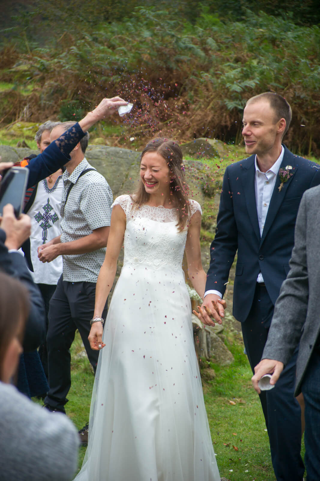 Bride and groom showered with dried petal confetti