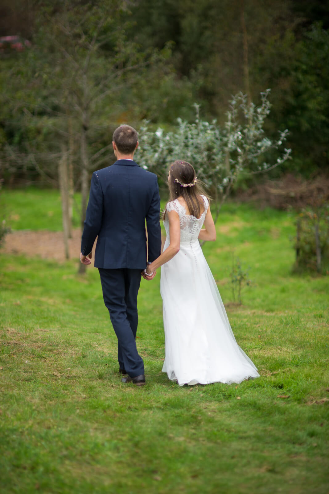 Bride and groom walking away down a grassy slope