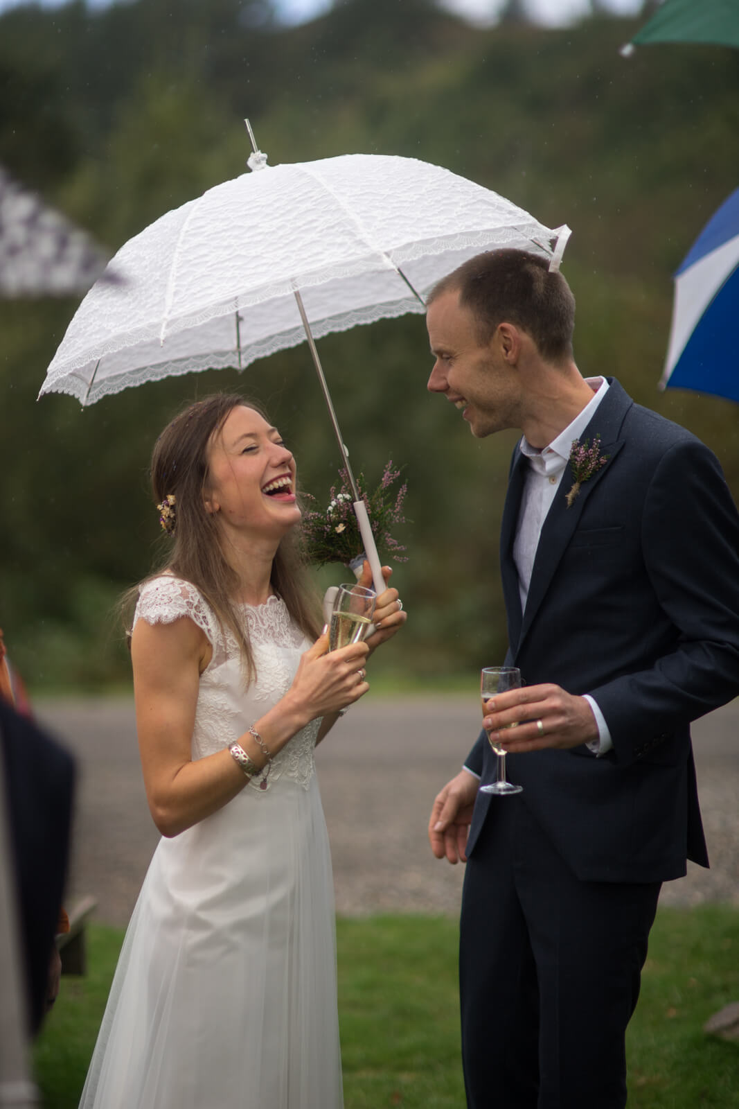 Bride and groom with champagne lauging under a white lace umbrella