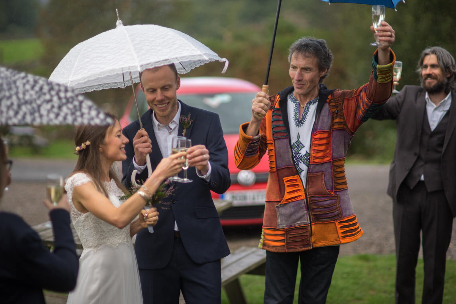 Bride groom and celebrant toast with champagne under umbrellas