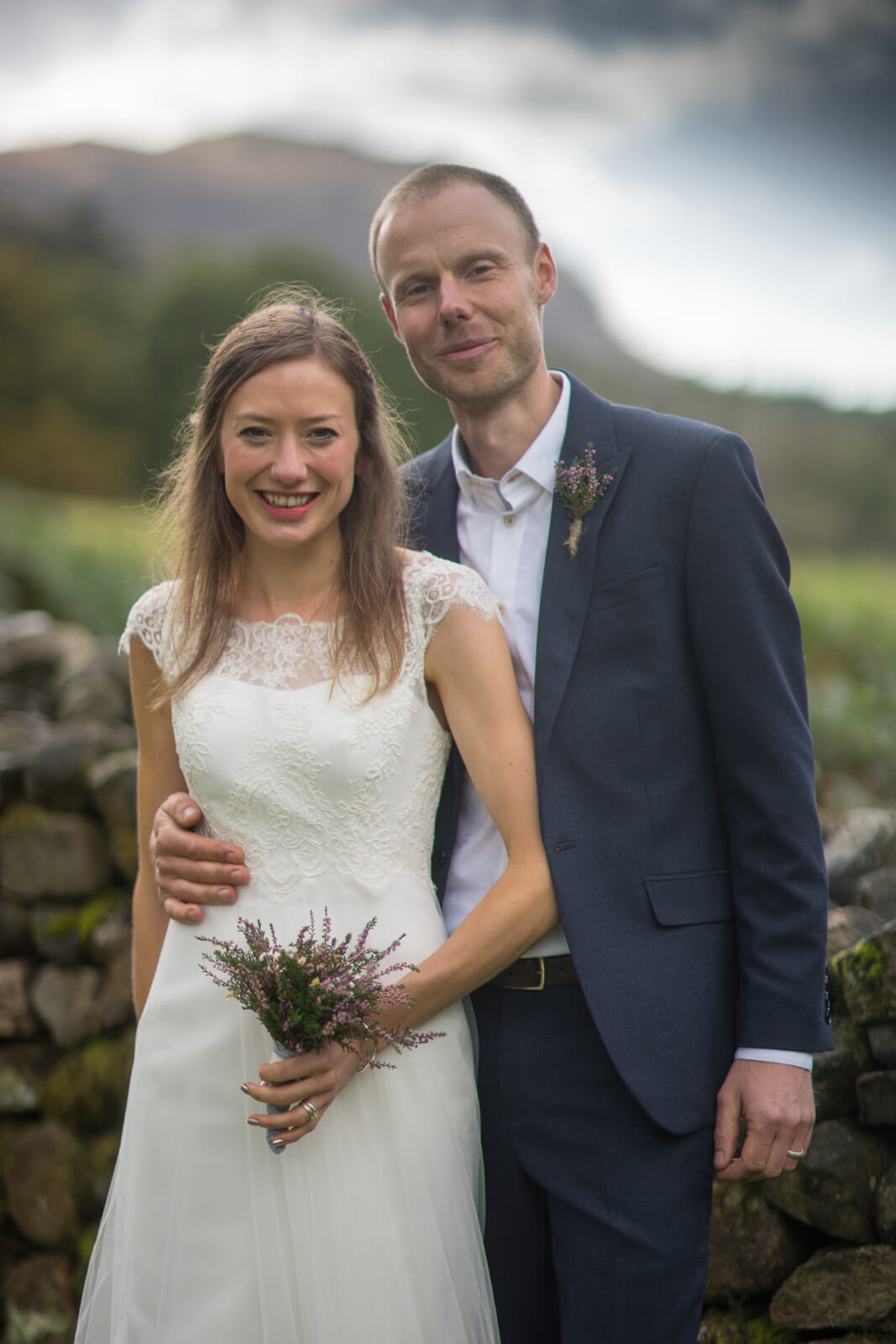 Bride and groom infront of mountains and dry stone wall