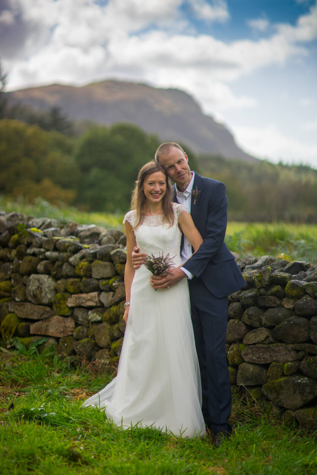 Bride and groom leaning against stone wall in the lake district