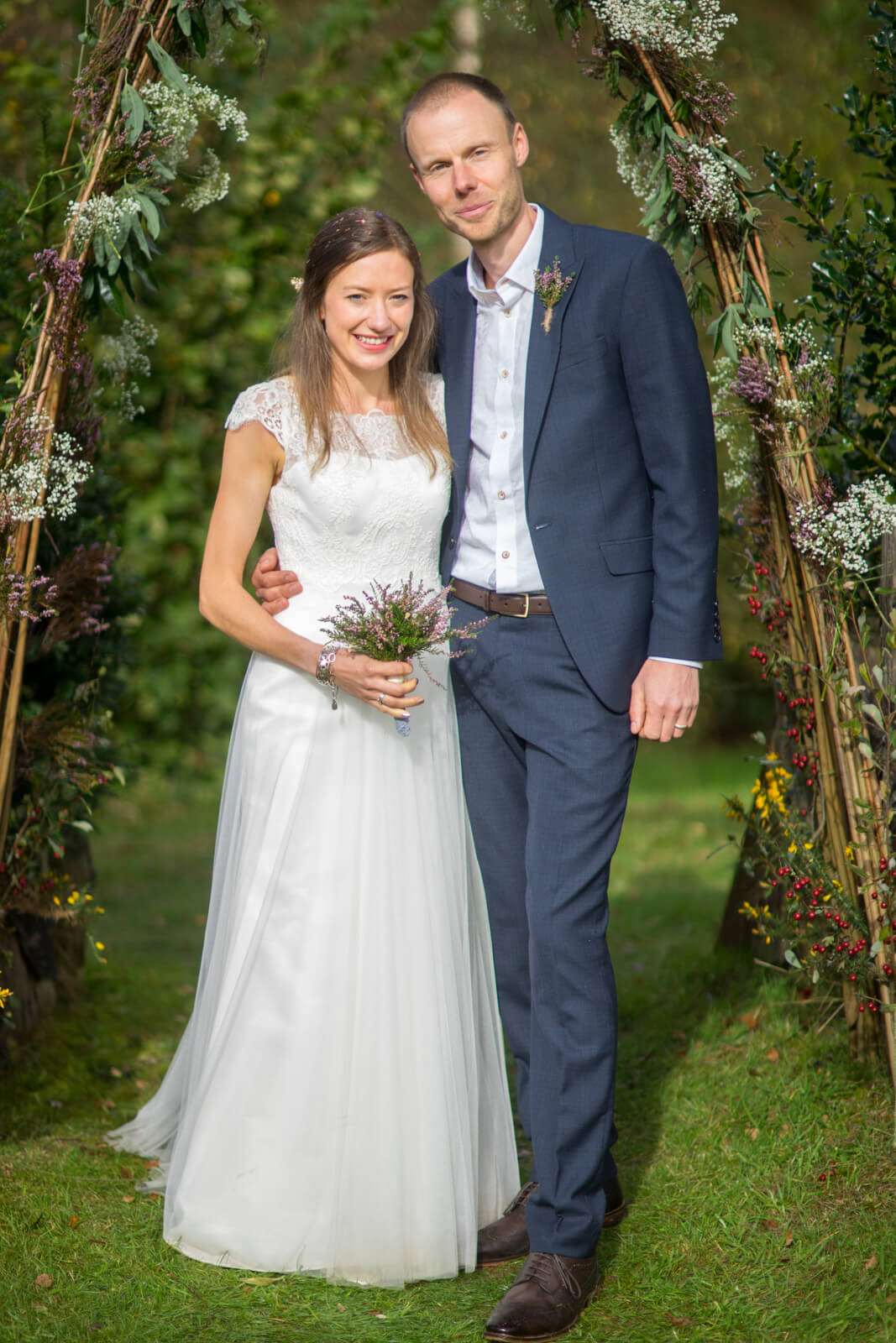 Bride and groom under a willow flower arch