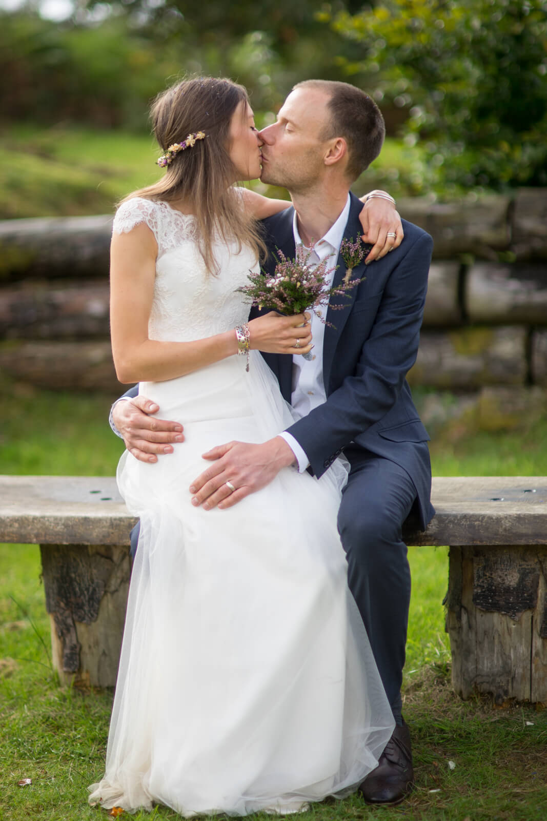 Bride sitting on grooms knee kissing on a bench