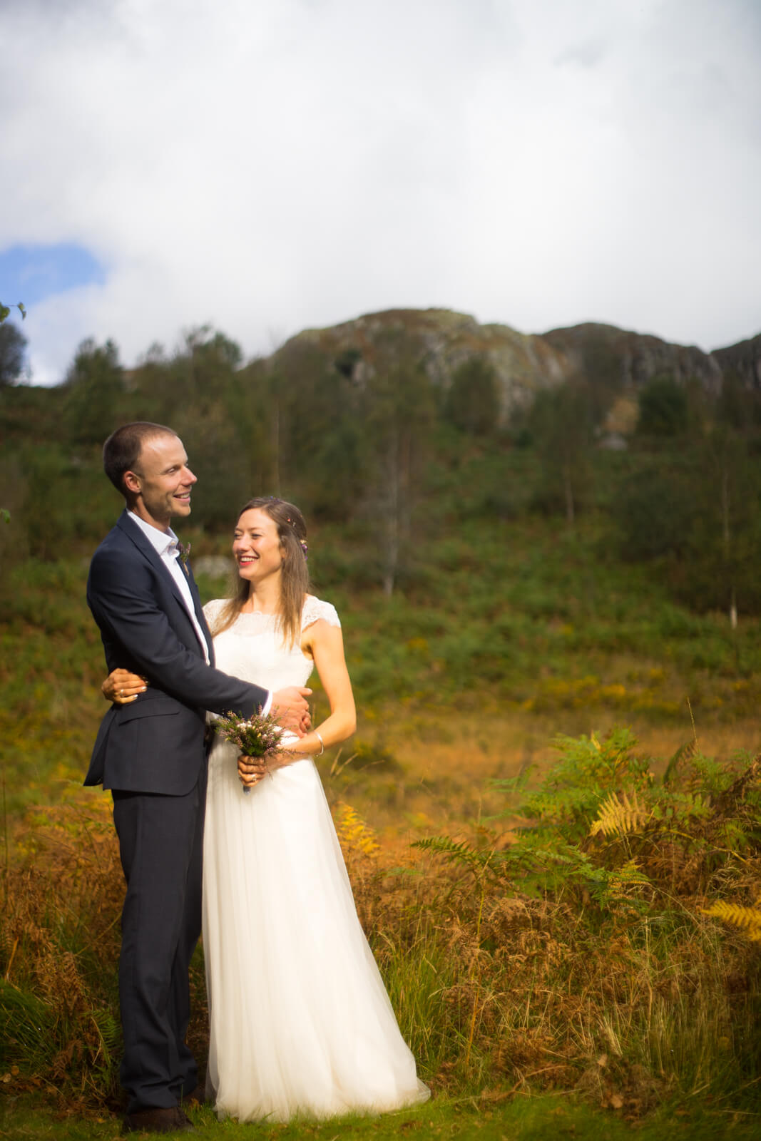 Bride and groom against background of hills and autumn bracken