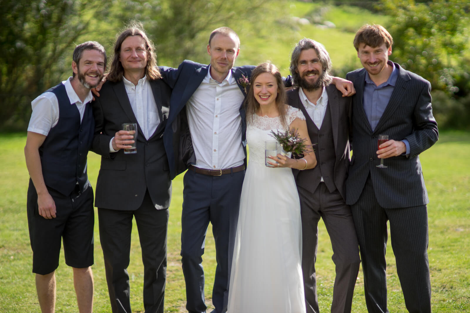 Bride and groom with arms around four groomsmen