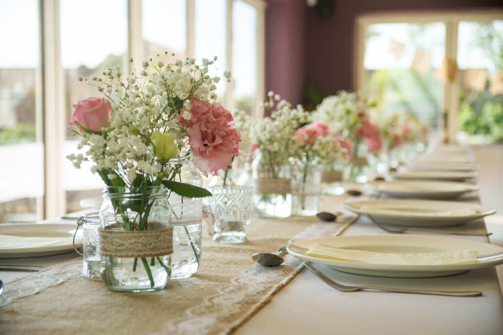 Table set with pink and white flowers, burlap and hessian