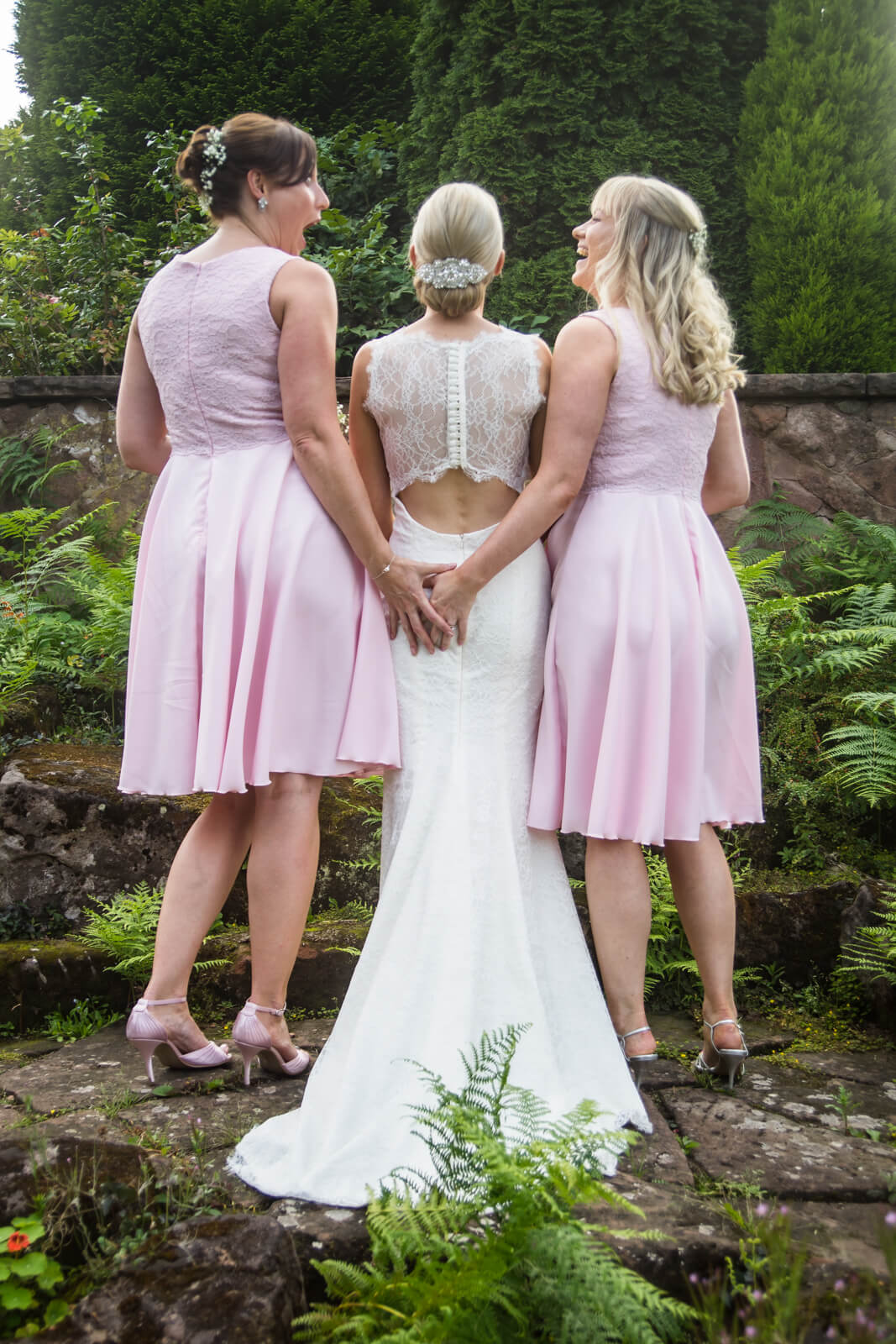 Two bridesmaids in pink pinch the bride's bum