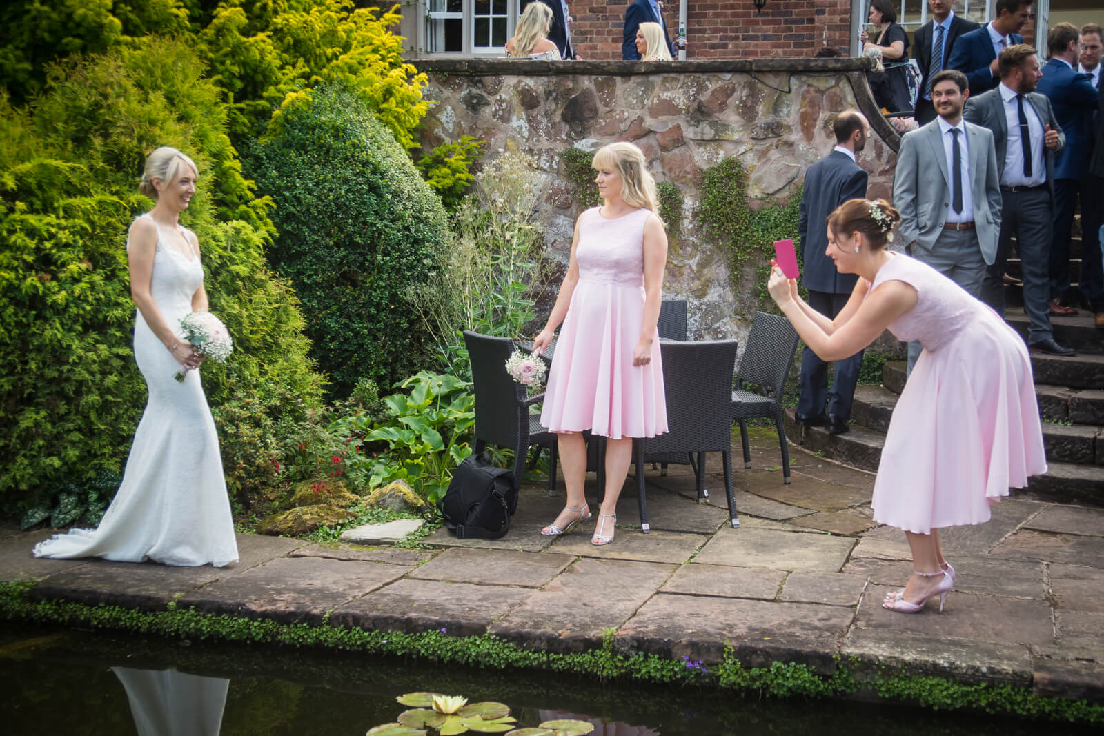 Bridesmaids take pictures of the bride on their mobile phones