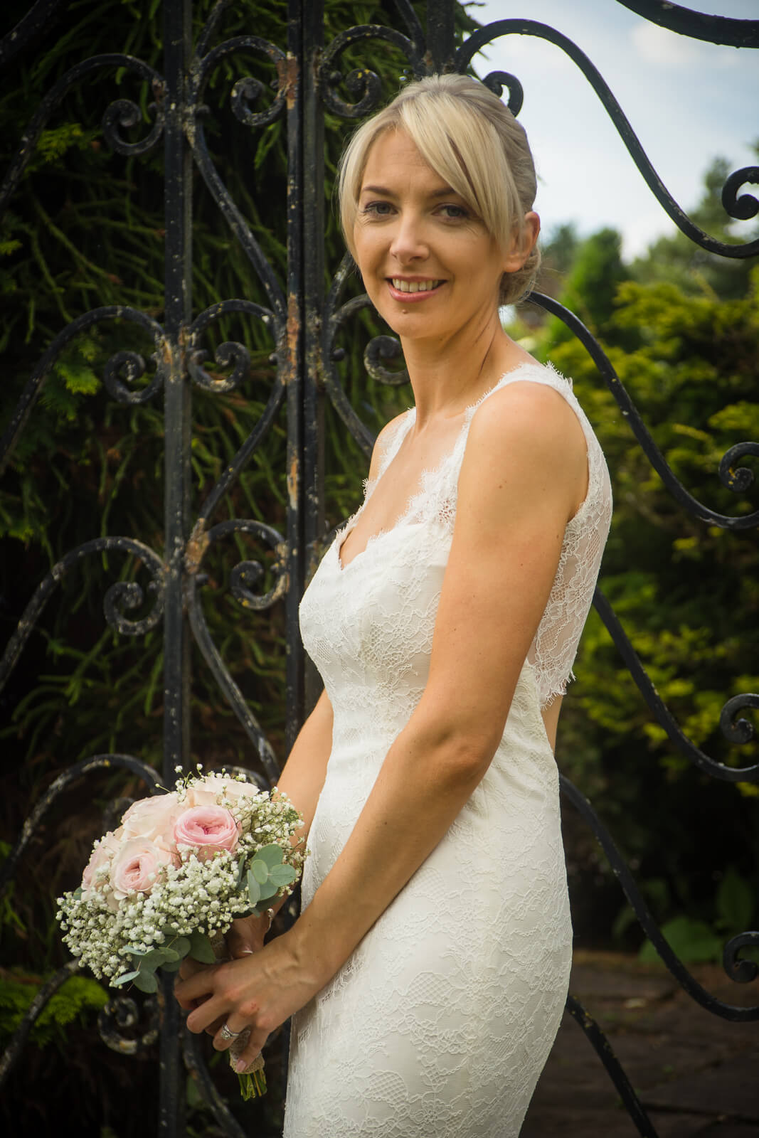 Portrait of the bride with pink rose bouquet against iron gate.