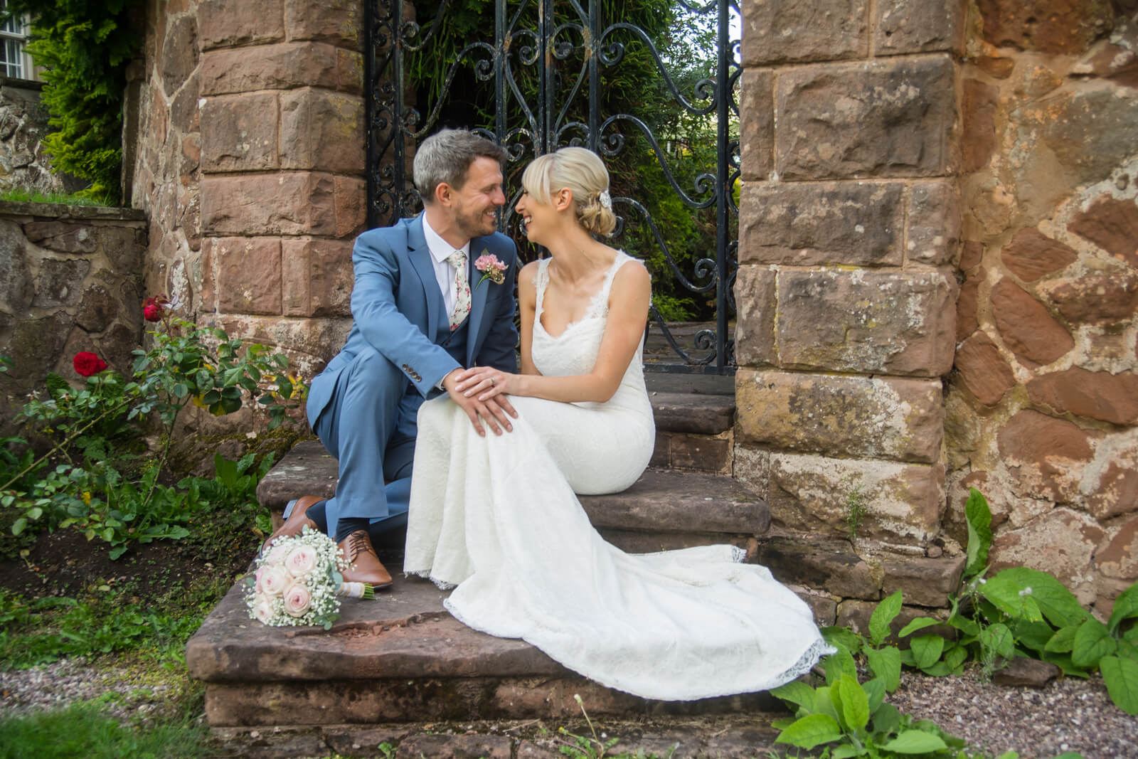 Bride and groom sit facing each other on steps in front of a garden gate