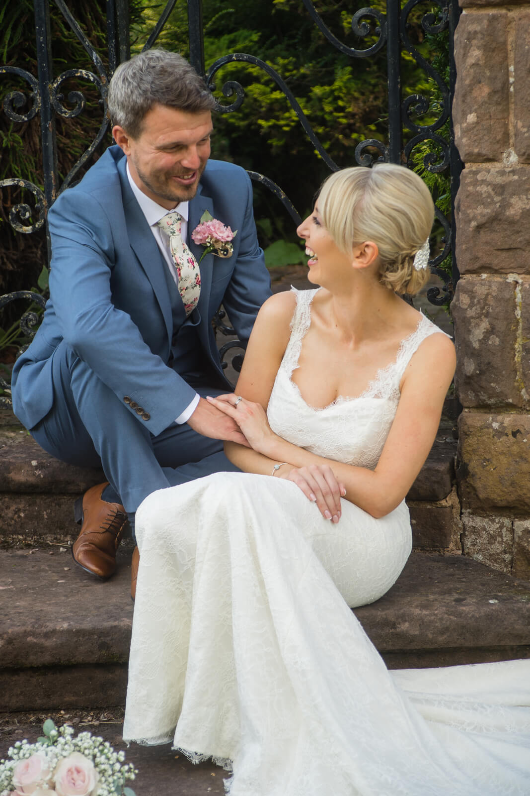 bride and groom sitting on garden steps laughing together
