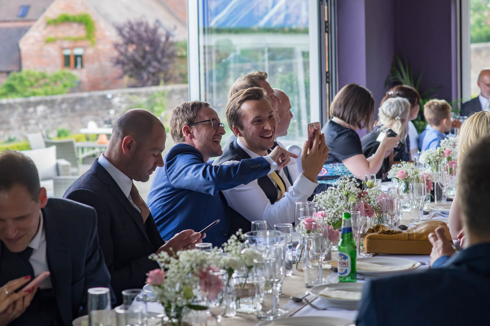Guests at the wedding breakfast lauging at a mobile phone