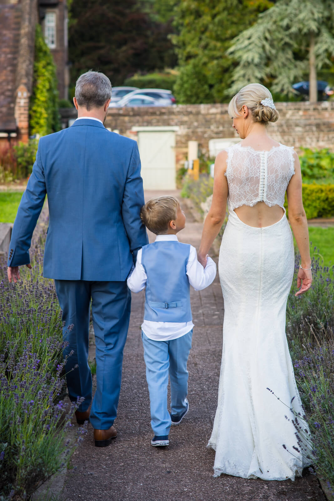 Bride and groom walk away through a lavender garden with son between them