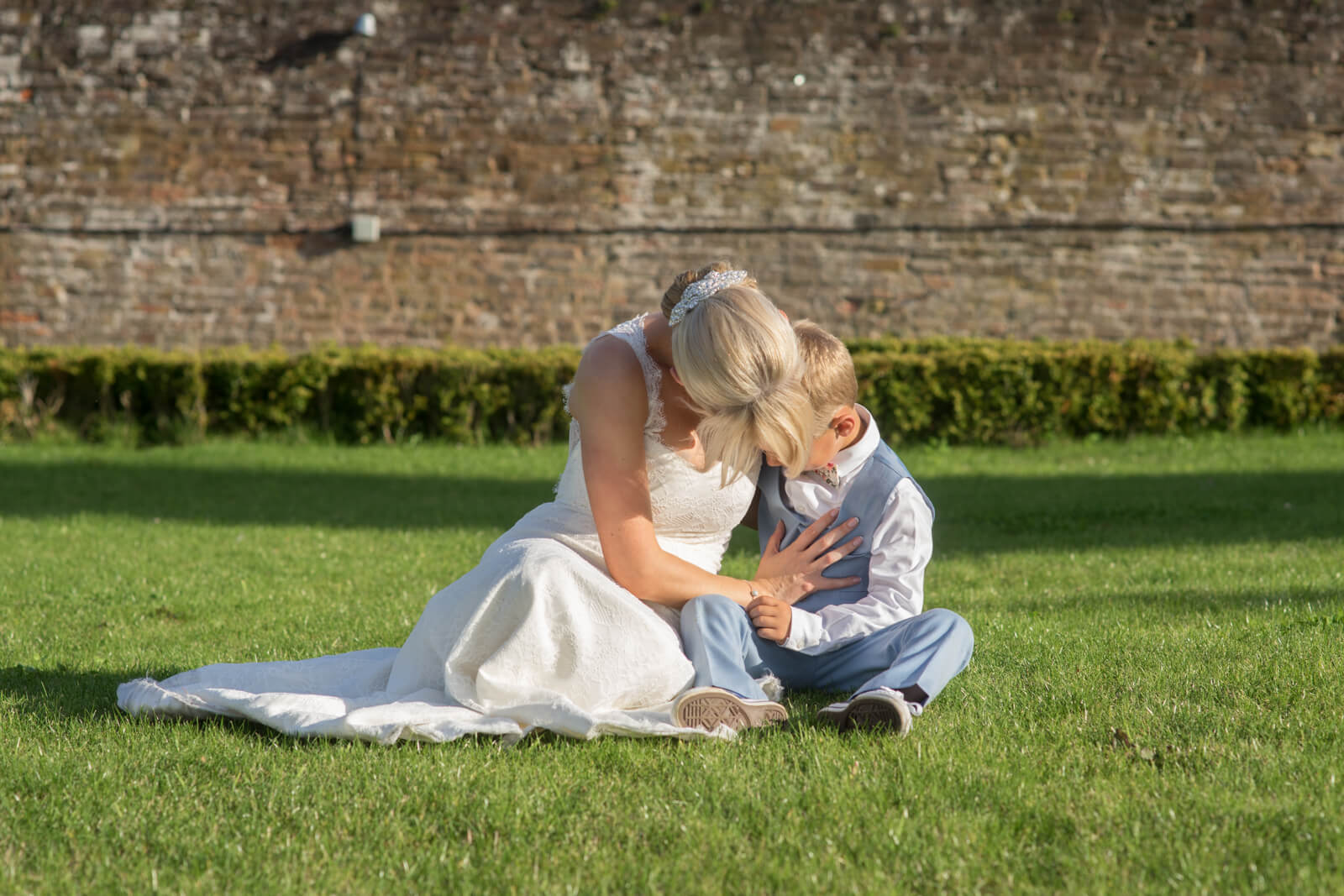 Bride and son share a moment sitting on a lawn