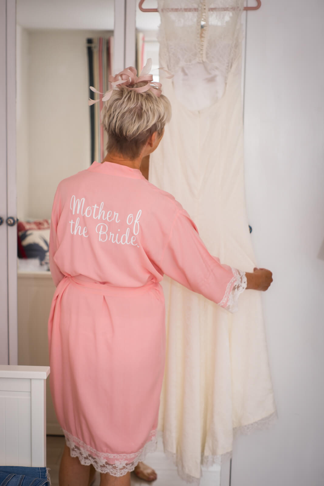 Mother of the bride in dressing gown admiring wedding dress