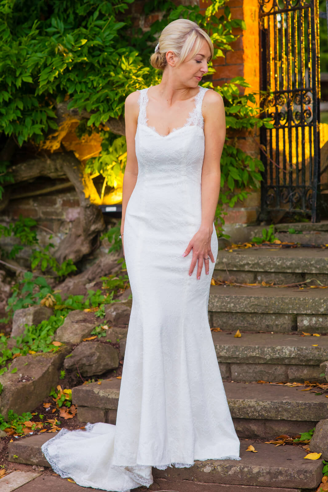 Bride stands infront of metal gate with golden evening sun