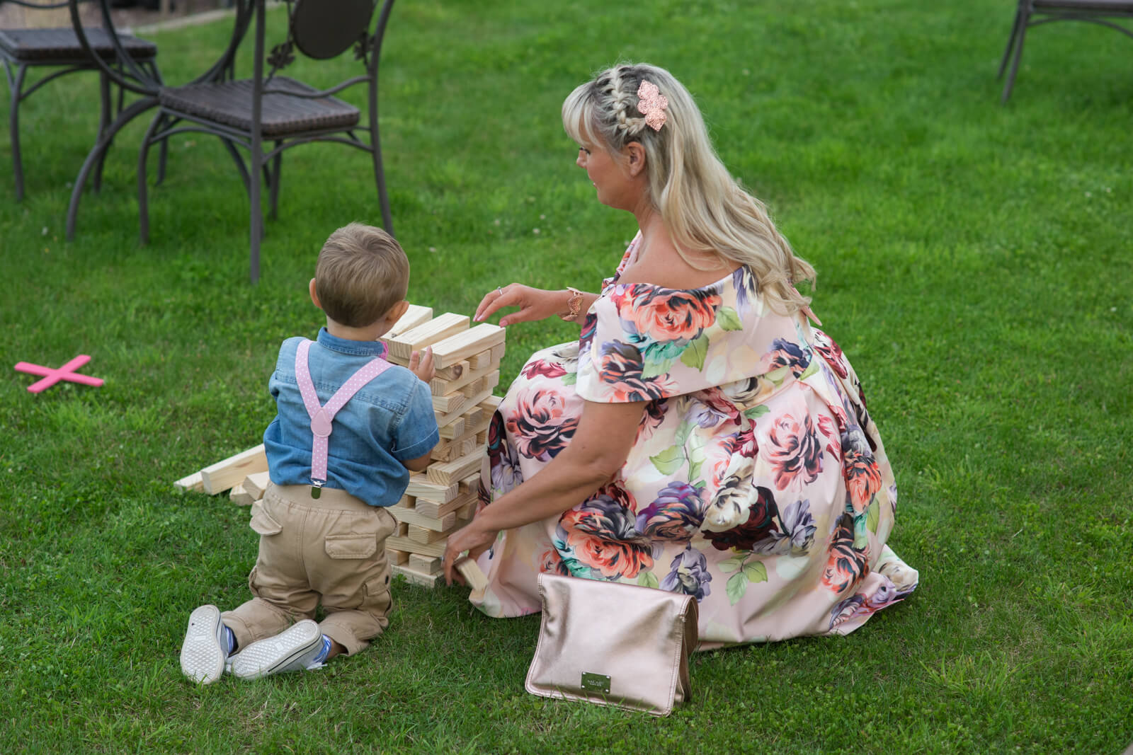 Lady and little boy play jenga lawn games during wedding reception