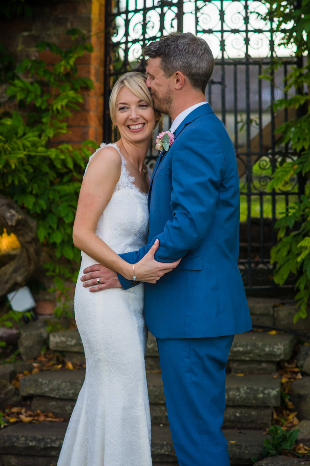 Groom kisses bride on the head infront of wrought iron gates