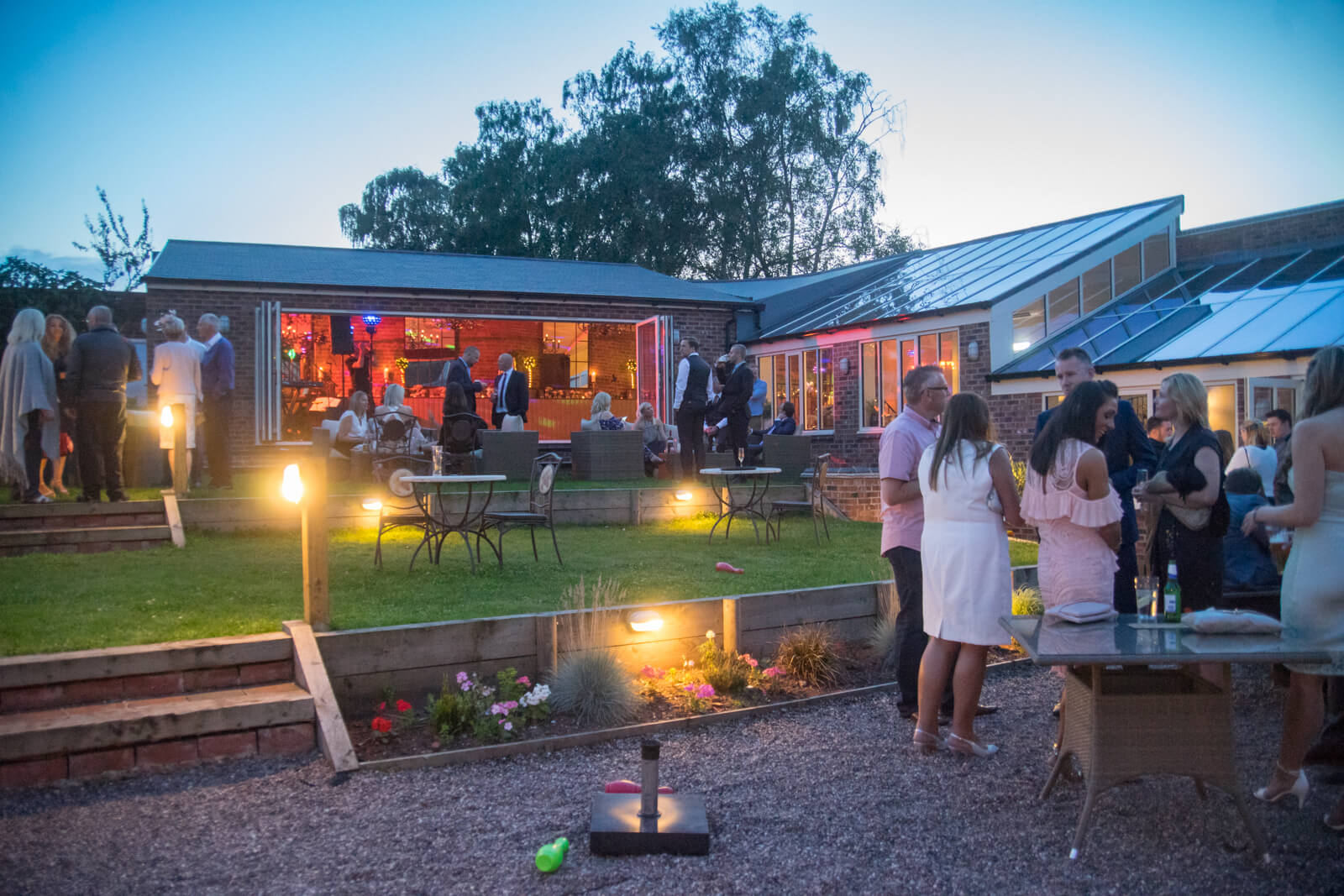 Guests socialising in the garden outside the wedding reception venue in the evening light
