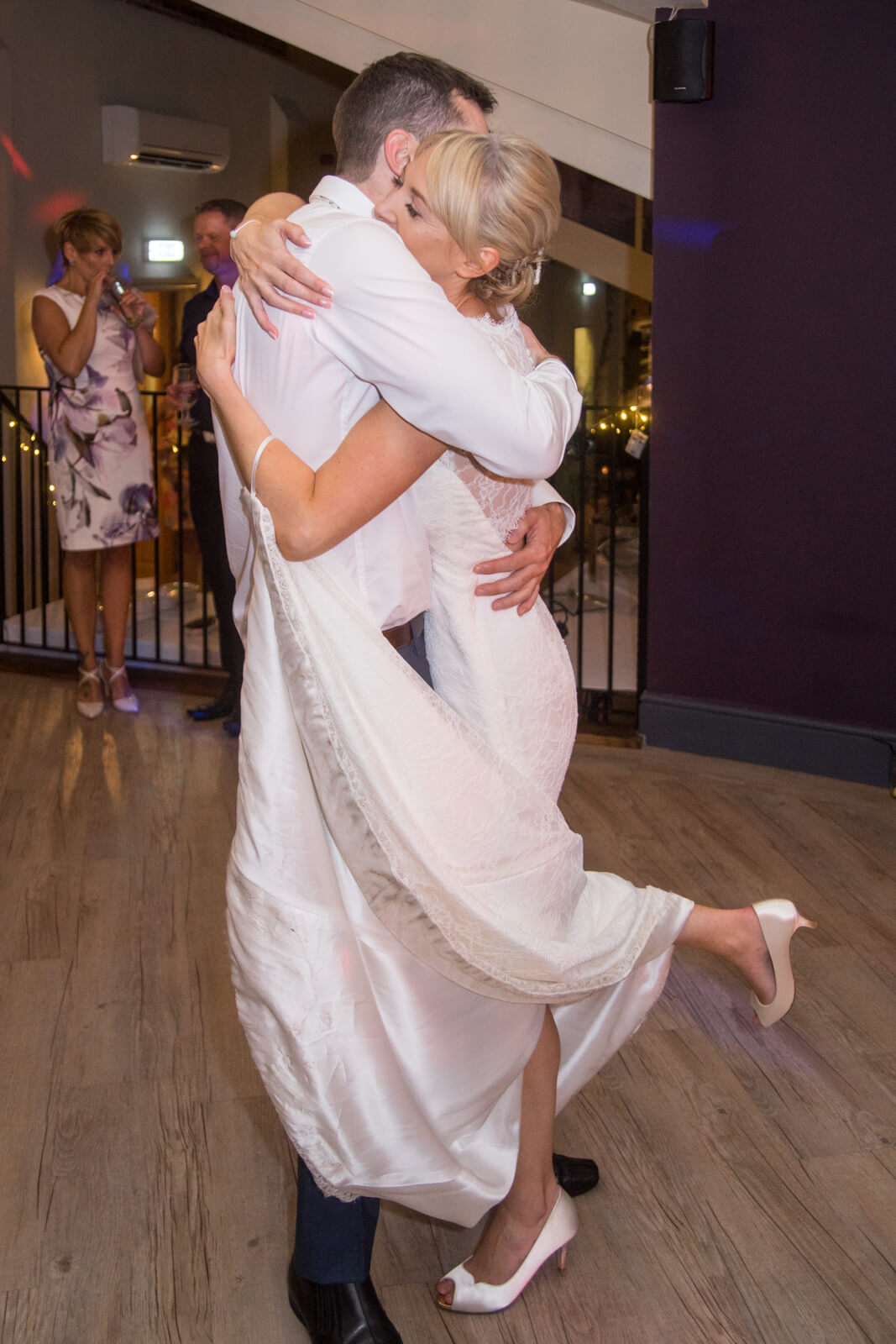 Bride and her brother hugging on the dance floor