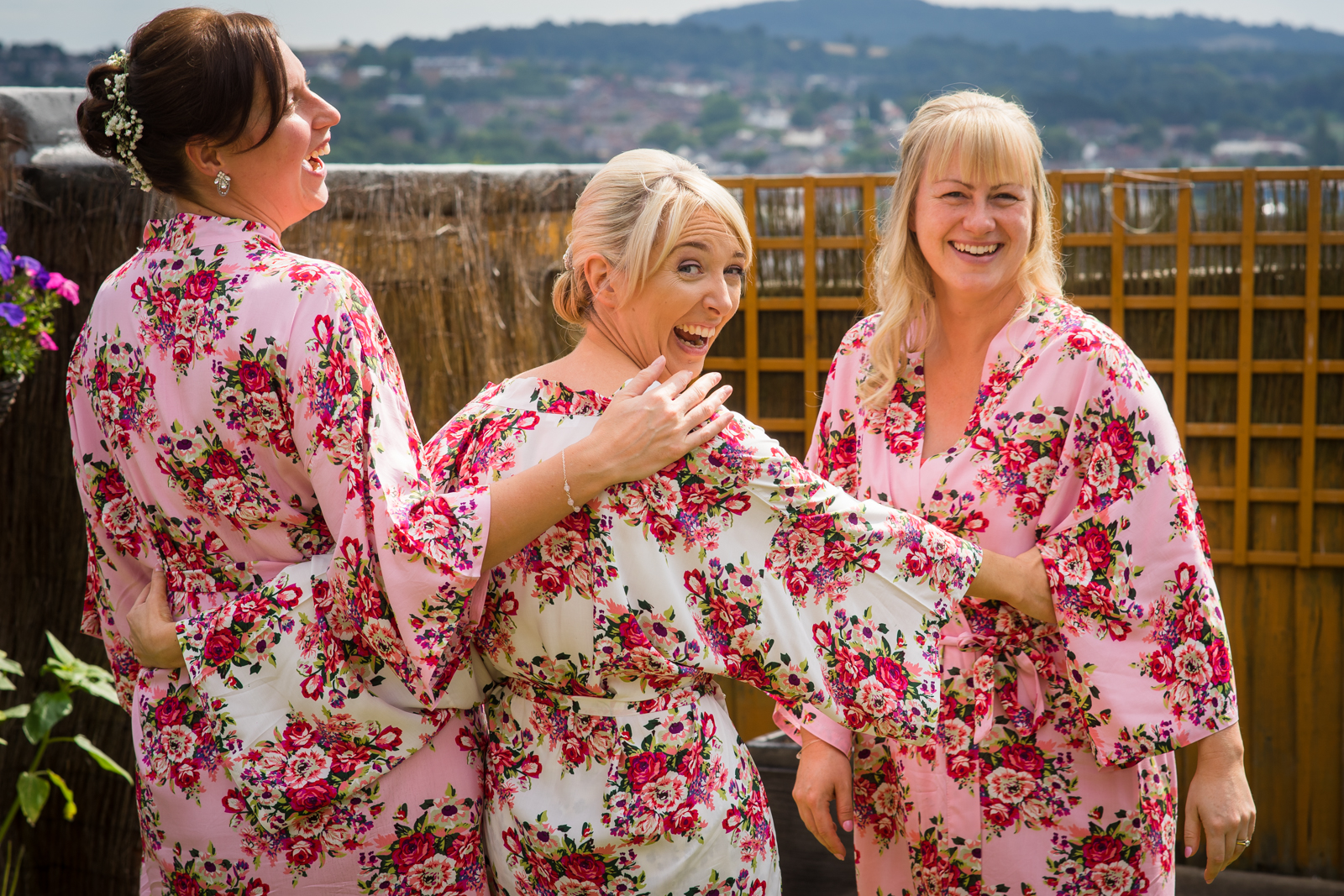 Bride and two bridesmaids in matching dressing gowns laughing