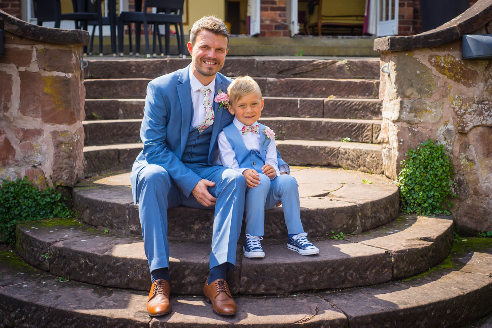 Groom and his son sitting on steps outside