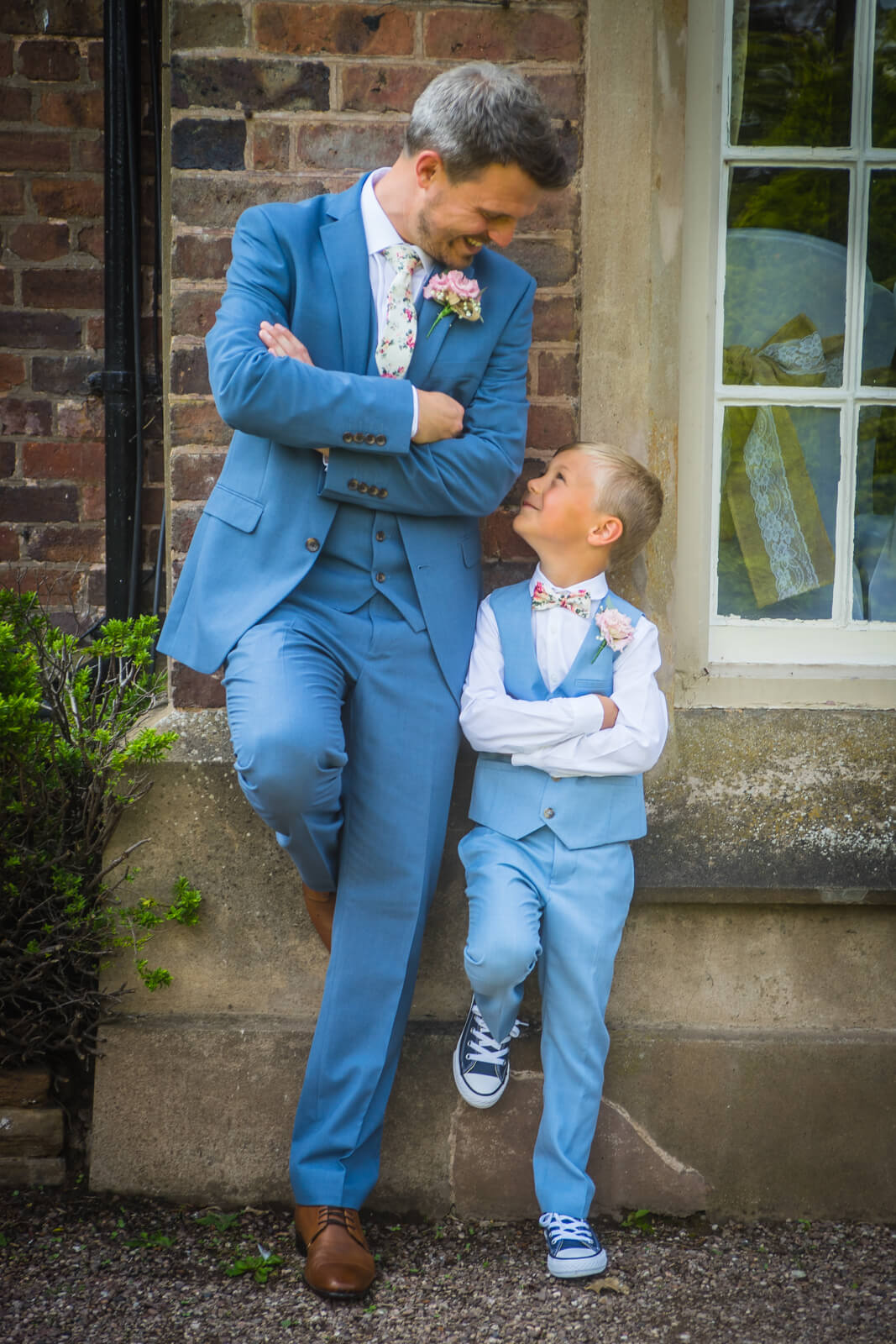 Groom and his son leaning casually against a wall