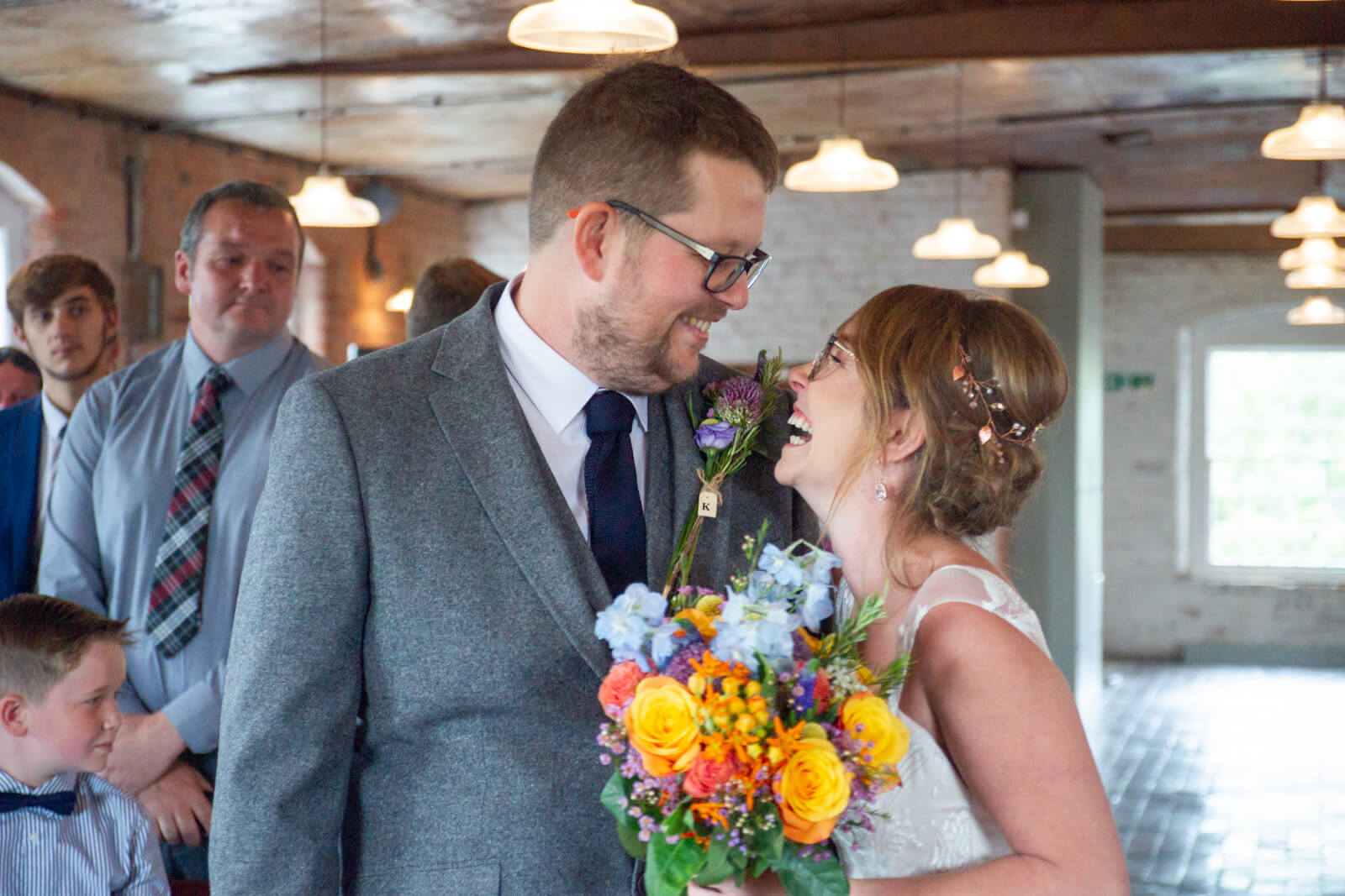 Bride and groom laugh together as they meet at the alter