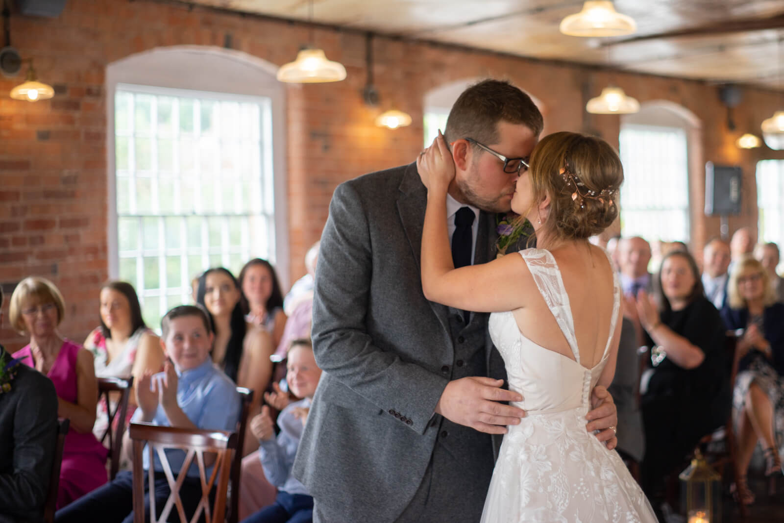 bride and groom kiss while guests applaud