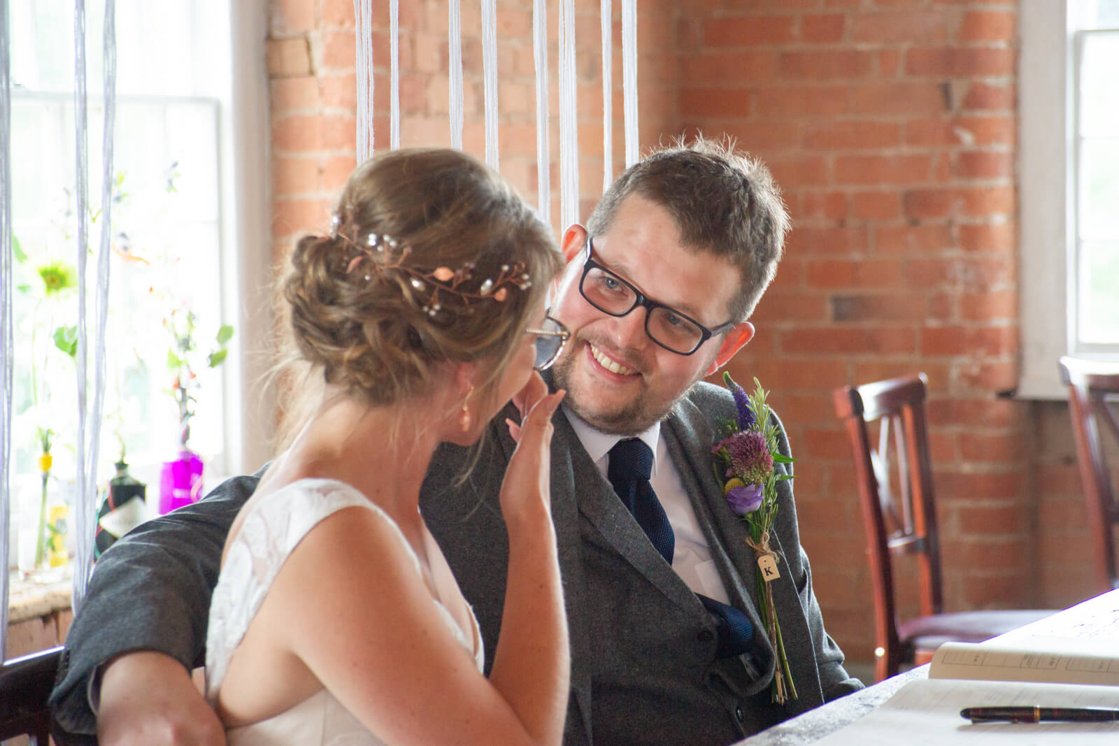 Groom looks at bride as she talks to him while signing the register