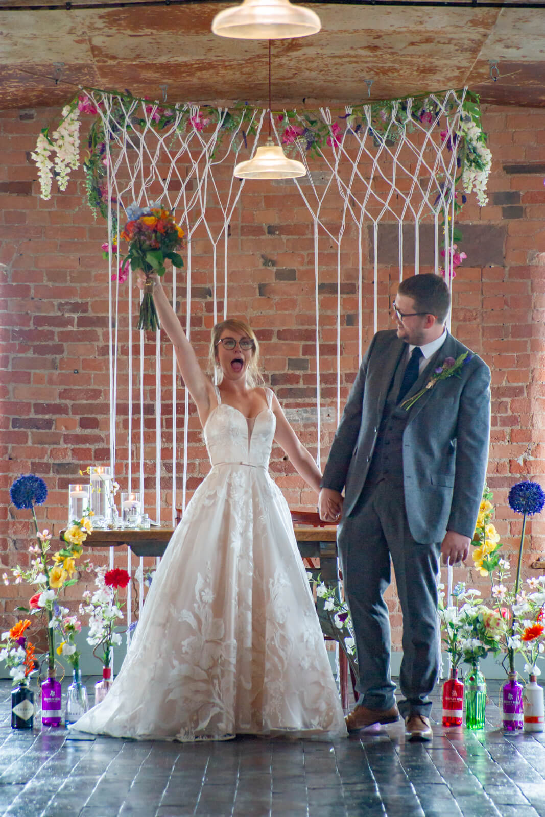 Bride waves her bouquet in the air in celebration