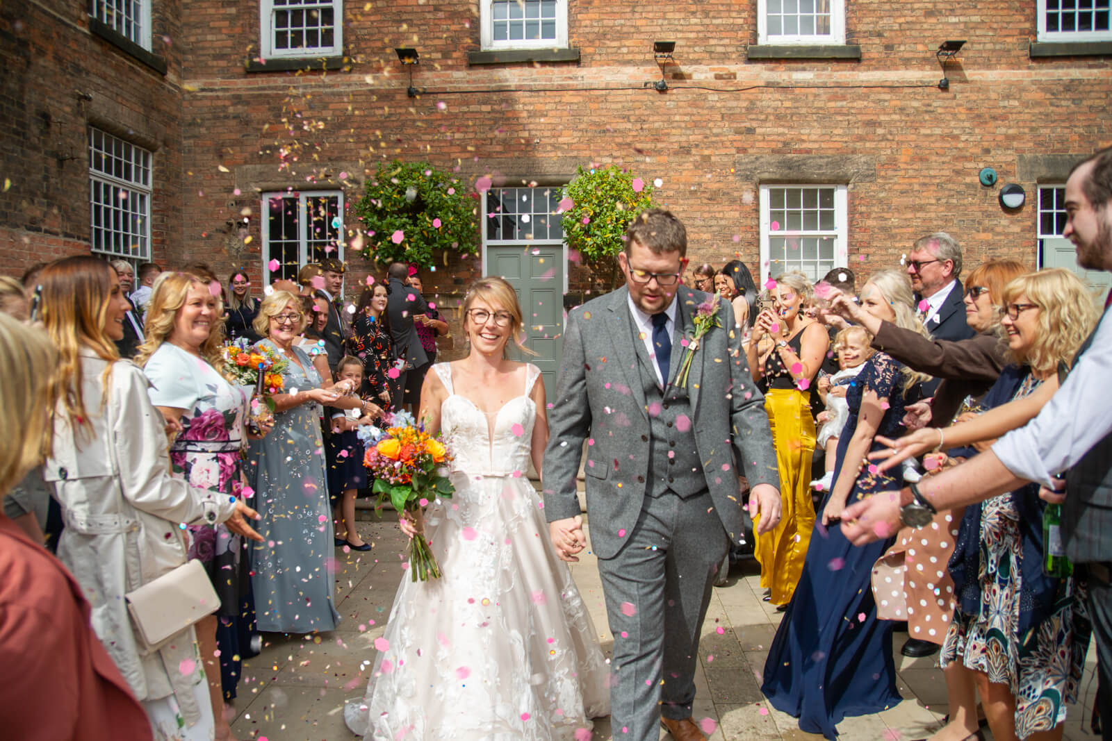 Bride and groom walk through their guests with confetti outside The West Mill Derby