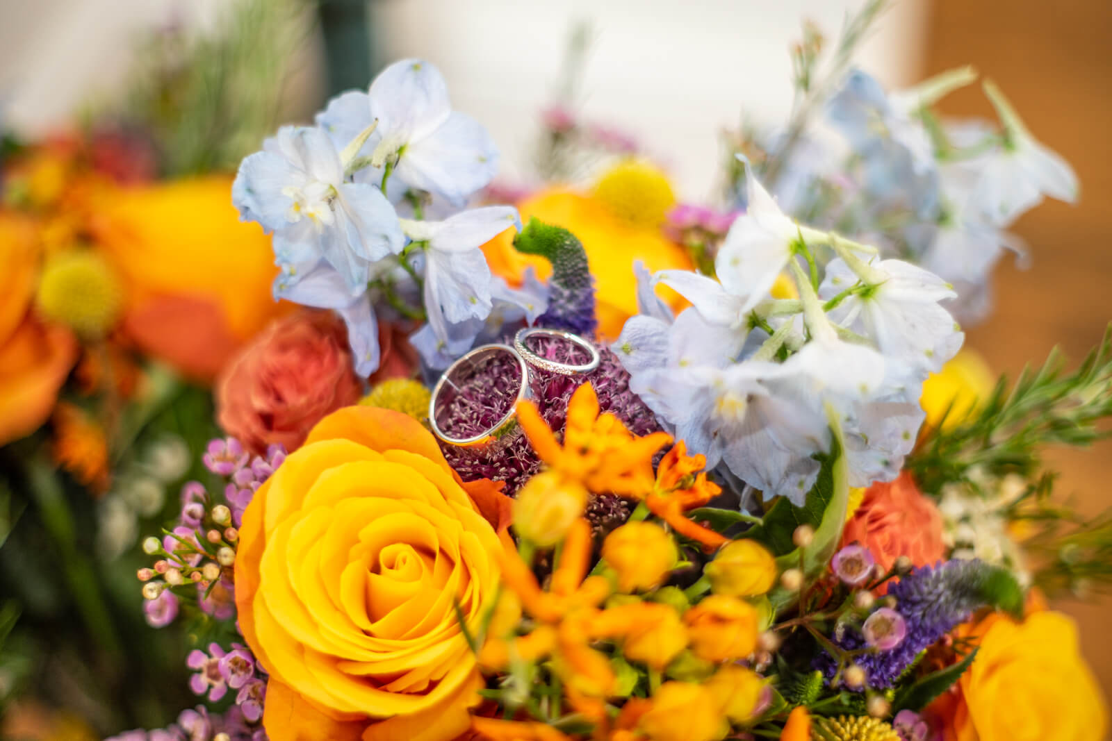 Wedding rings amongst brightly coloured summer flowers