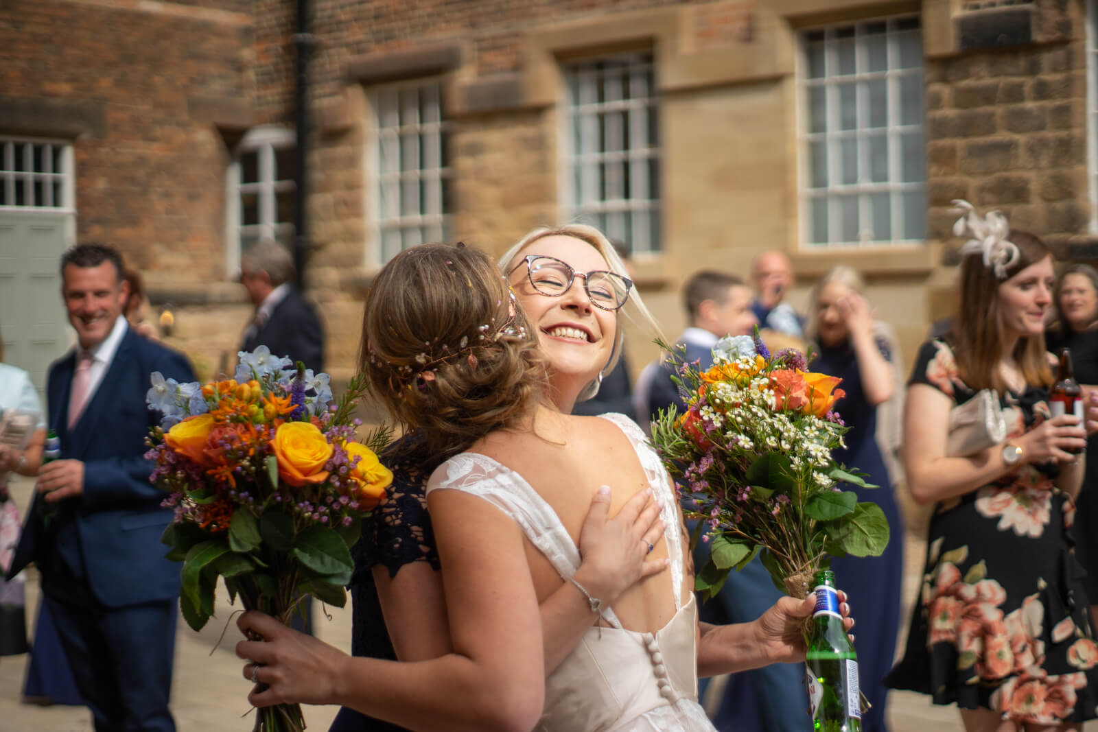 Bridesmaid hugs the bride with a big smile while both holding bouquets of colourful flowers