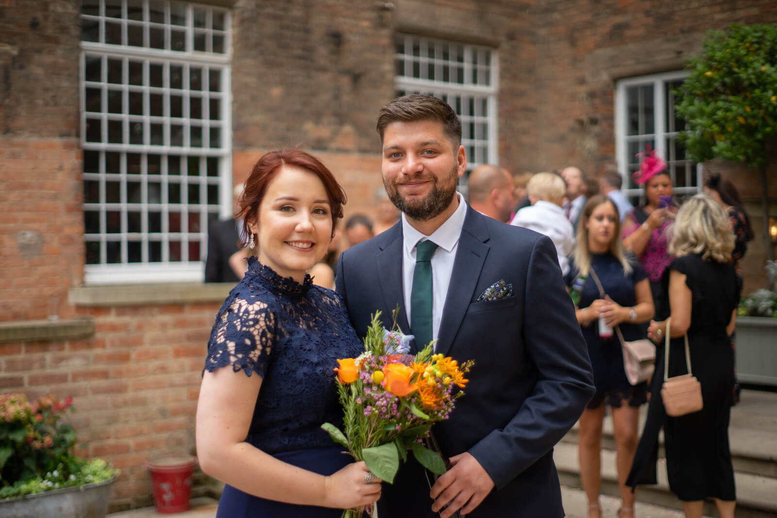 Bridesmaid and her partner in navy pose with a colourful bouquet
