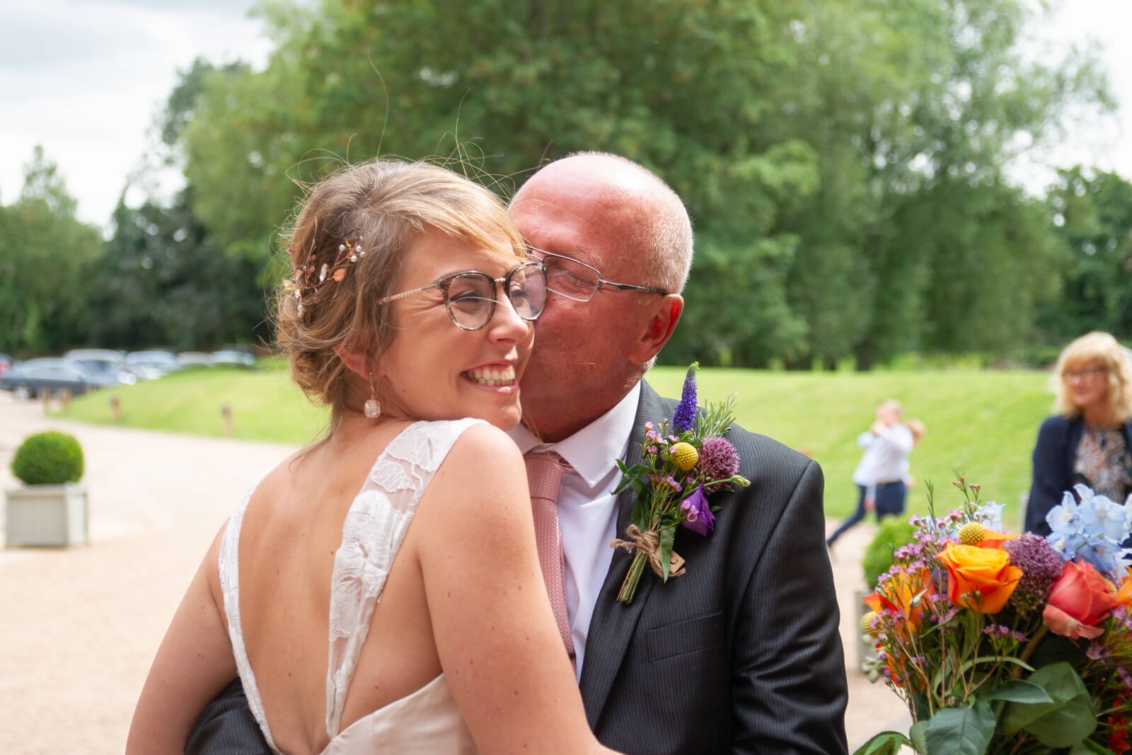 Father of the bride kisses her on the cheek while she grins