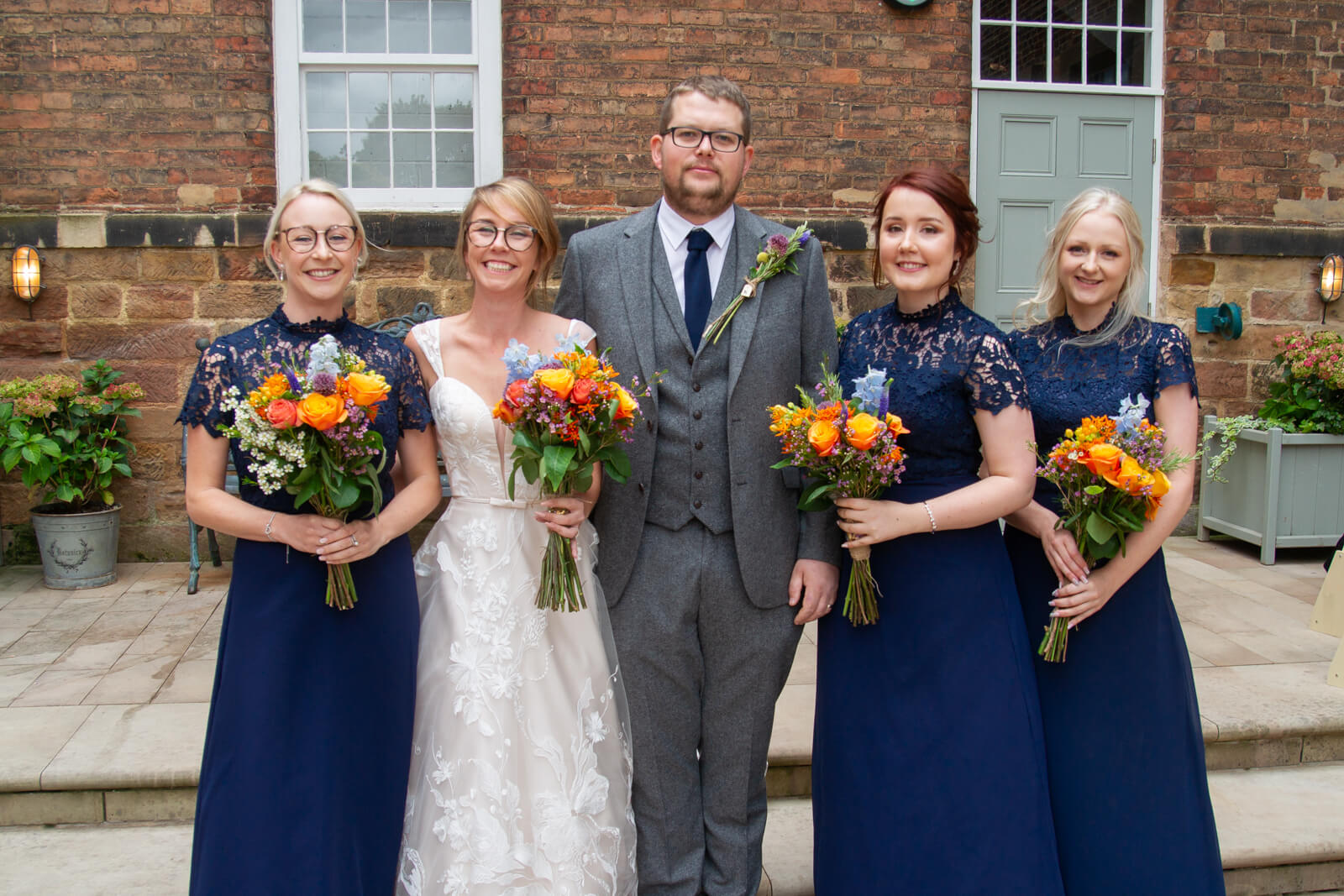 Bride and groom pose for a formal portrait with three bridesmaids